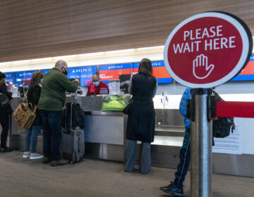 Travelers wearing protective masks check-in at the Delta Air Lines Inc. check-in counter