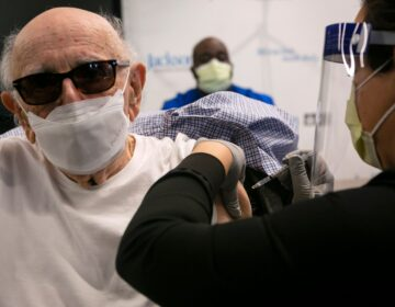 Norman Einspruch, 88, a cardiology patient at Jackson Memorial Hospital in Miami, Fla., receives his first dose of the Pfizer-BioNtech COVID-19 vaccine