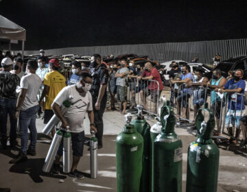 People wearing protective masks wait in line to refill oxygen tanks in Manaus