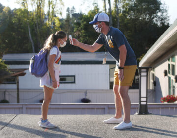 Nathan Grebil (right) takes the temperature of fourth-grade student Hyla during a health screening at Bel Aire Elementary School in Tiburon, Calif., in October.
