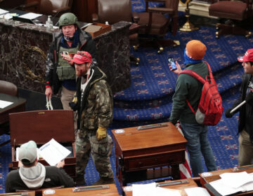 Larry Rendall Brock Jr., an Air Force veteran, is seen inside the Senate Chamber wearing a military-style helmet and tactical vest during the rioting at the U.S. Capitol. Federal prosecutors have alleged that before the attack, Brock posted on Facebook about an impending