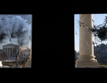 The U.S. Supreme Court is seen through a broken window at an entrance of the U.S. Capitol