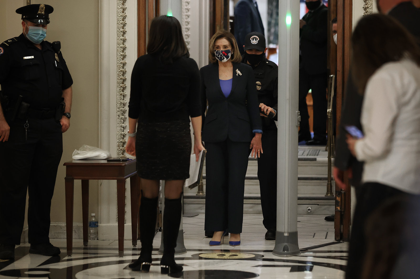 Speaker of the House Nancy Pelosi, D-Calif., is screened at a metal detector at the doors of the House of Representatives Chamber