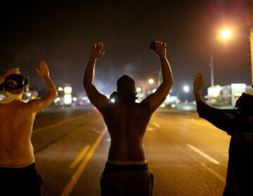 Demonstrators raise their arms and chant,