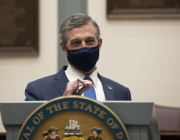 Delaware Gov. John Carney, wearing a face mask, speaks at a podium
