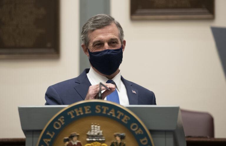 Delaware Gov. John Carney, wearing a face mask, speaks at a podium