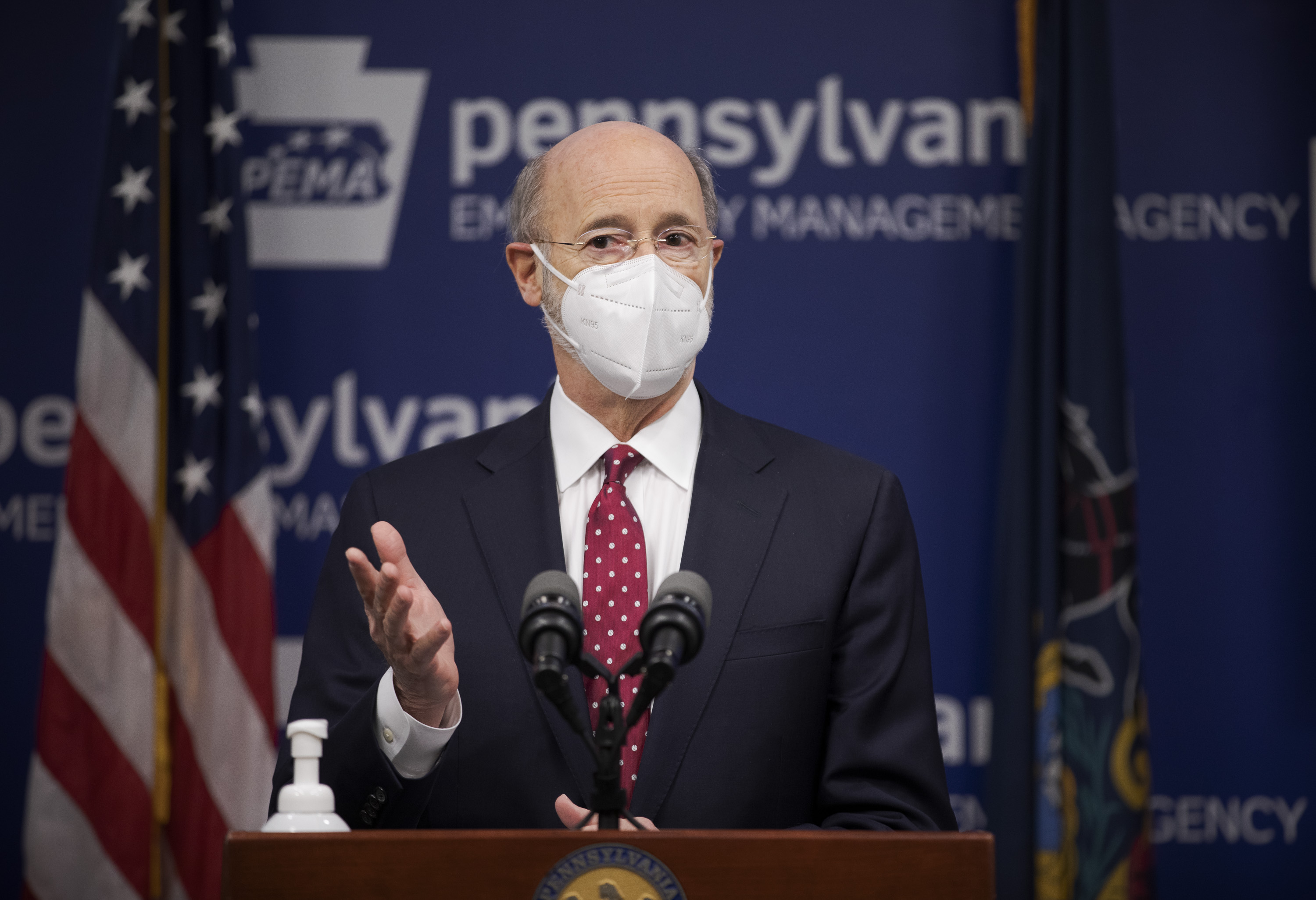 Gov. Tom Wolf, wearing a face mask, speaks to the press from behind a podium