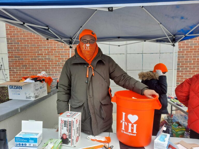 Matthew George bundled up outside in Germantown, next to a bright orange trash can