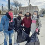 Kimberly Robinson Calland, standing with family and friends, holds a garbage bag as the group helps clean up a Germantown street