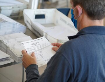 An elections worker processes a mail ballot.