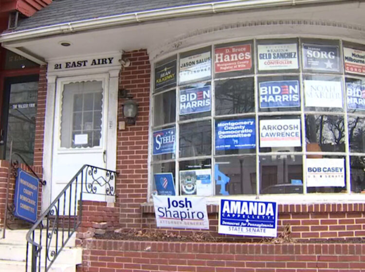 Multiple campaign signs and posters, including some supporting President Joe Biden and Vice President Kamala Harris, adorn the front window of the Montgomery County Democratic Committee's Norristown office. (NBC10)