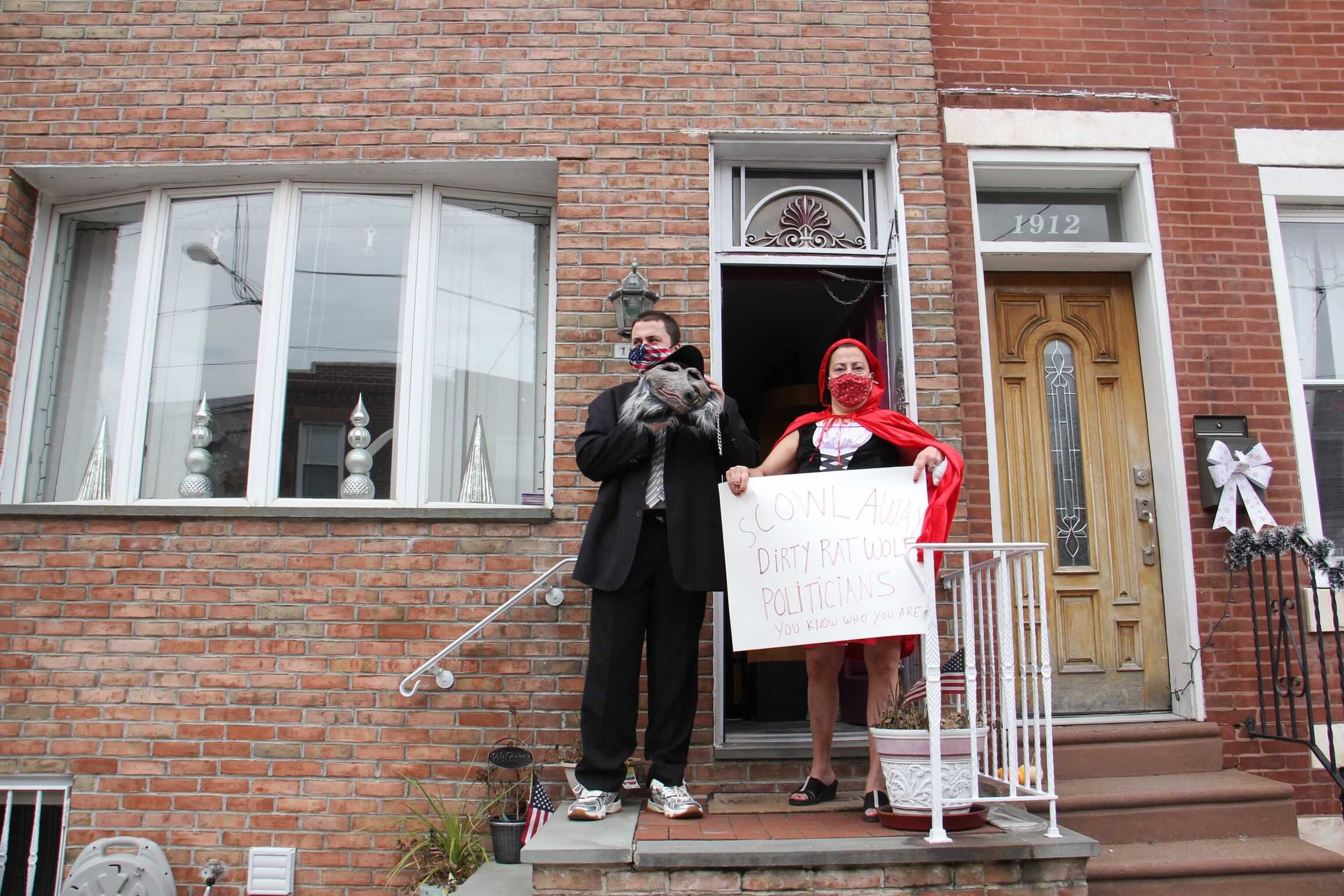 Maureen Fratantoni, dressed as Little Red Riding Hood, and her son, son James Fratantoni, the big bad wolf-rat, show support for those protesting the cancellation of the Mummers Parade from their front stoop on 11th Street.