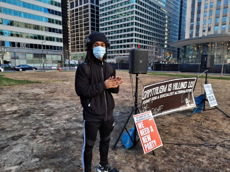 Jaja Robinson wears a face mask in front of signage at a Socialist Alternative meeting