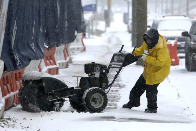 A man works to turn his snow-clearing machine