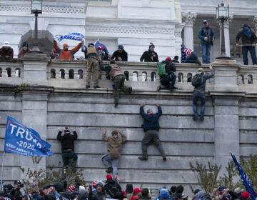 Supporters of President Donald Trump climb the west wall of the the U.S. Capitol on Wednesday, Jan. 6, 2021, in Washington.