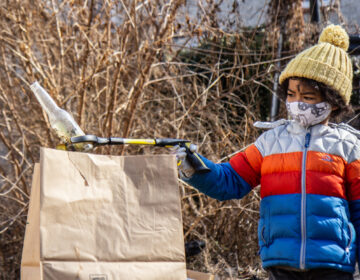 Eiji Mizukane places a glass bottle into a paper trash bag during a North Philly cleanup