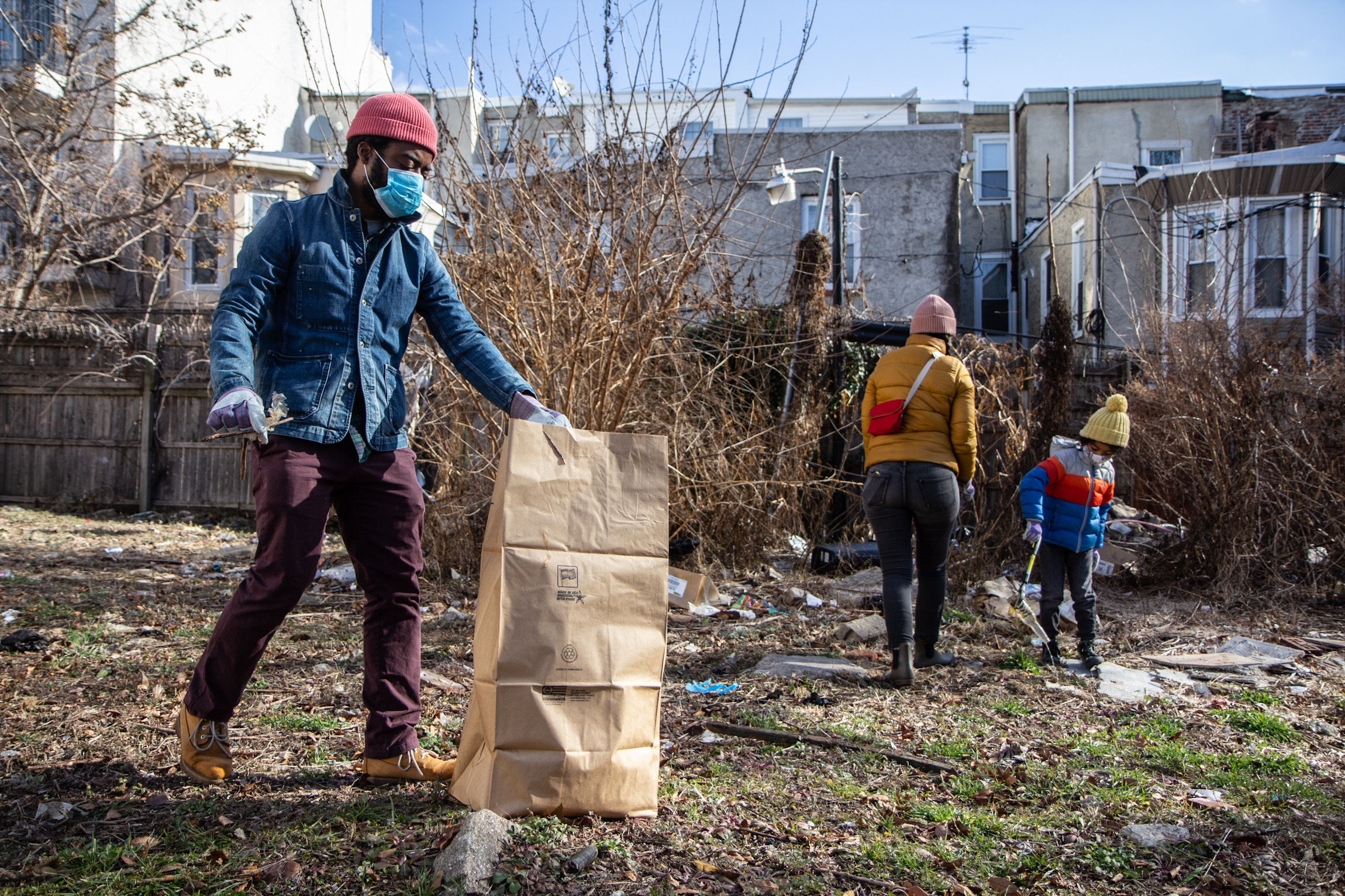 Robert Thompson (left), his wife, Eri Mizukane, and their 6-year-old son, Eiji, clean up a North Philly lot