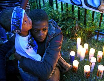 At a May 2019 vigil for Michael Thomas in Camden, Thomas' son, Major Thomas is embraced by Michael Thomas' brother, Shaqjuan Randall. (April Saul / WHYY)