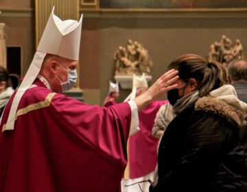 A priest uses his thumb to draw a cross of ashes on the forehead of a parishioner during an Ash Wednesday Mass at the Basilica of Saints Peter and Paul in Philadelphia. (Emma Lee/WHYY)