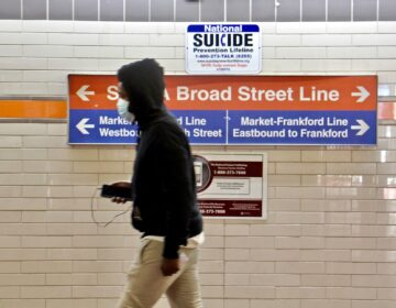 A SEPTA passnger walks toward the subway entrance. (Emma Lee/WHYY)
