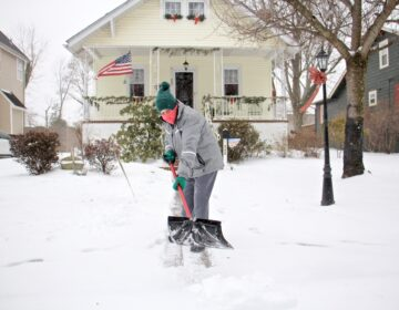 A Moorestoown, N.J., resident clears the snow in front of her house