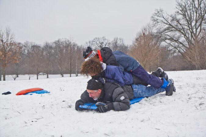 Mark Gamba, his son Luke, and friend Elias Zarin share a sled at Belmont Plateau in Philadelphia.