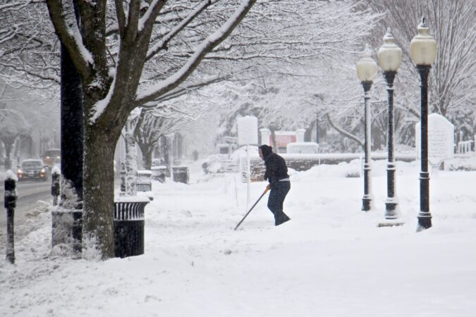 A shoveler clears the walkway to Our Lady of Good Counsel Church