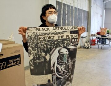 Anne Ishii, executive director of the Asian Arts Initiative, holds a poster designed by Philadelphia poet and musician, Moor Mother, for the Unity at the Initiative exhibit