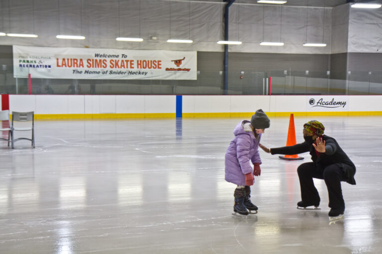 Skate instructor Sultana Afifiah helps a new skater at Laura Sims Skatehouse in Philadelphia. The city's rinks are reopening with COVID restrictions in February. (Kimberly Paynter/WHYY