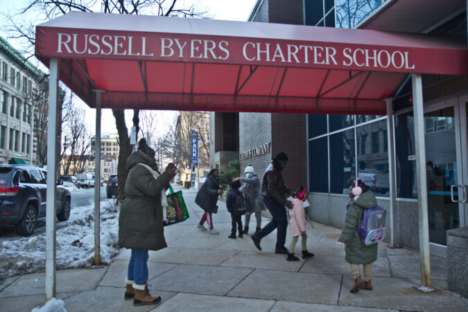 Sharon Stewart (left) takes a photo of her granddaughter (right) outside of Russell Byers Charter school