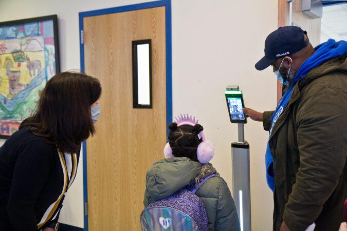 Sana Stewart, 6, receives a temperature check