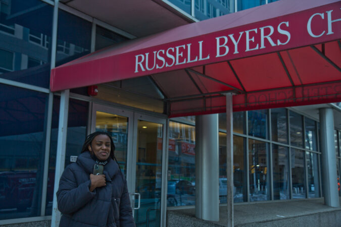 Sade Greenlee stands in front of Russell Byers Charter school