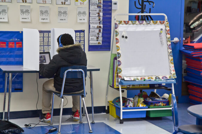 A student sits at a desk with physical barriers placed on either side