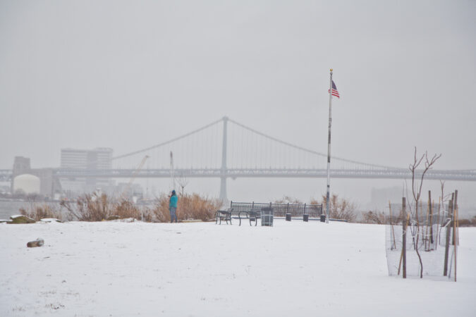 A person takes photos of the Delaware River at Penn Treaty Park in the snow