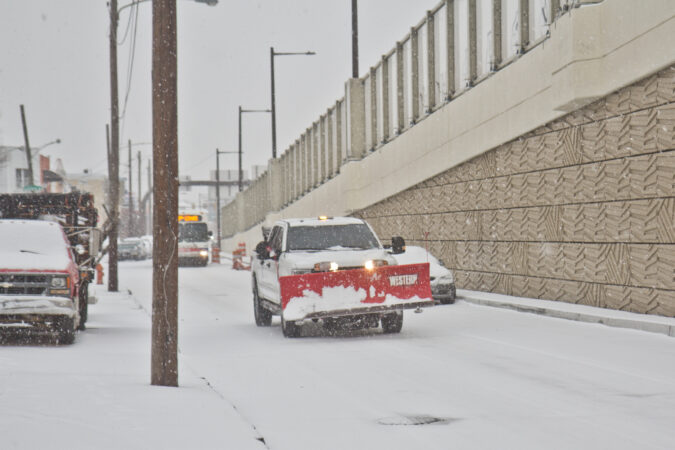 A plow truck rolls around Fishtown during a winter storm
