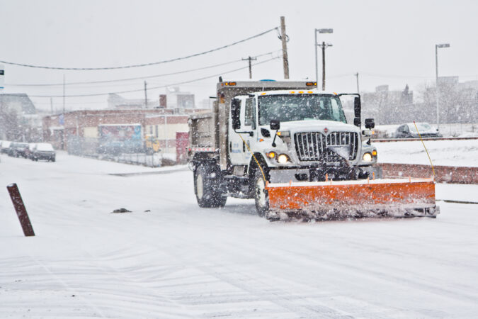 A city trash truck outfitted with a plow rolls down Cumberland Street