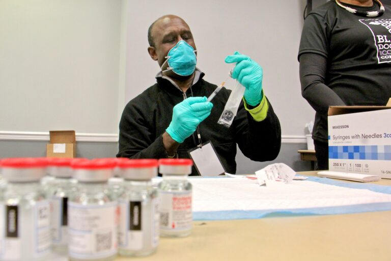 Dr. Christophe DeBrady of the Black Doctors COVID-19 Consortium prepares doses of vaccine for the hundreds who turned out for a mass vaccine clinic at the Liacouras Center at Temple University. (Emma Lee/WHYY)