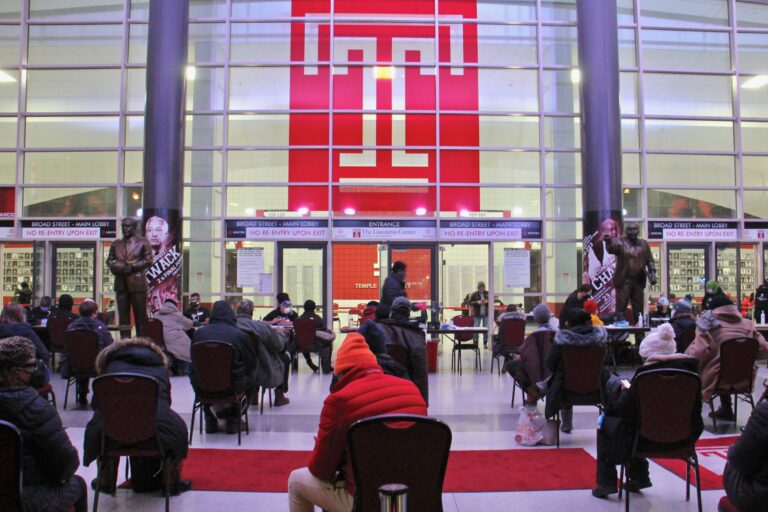 Philadelphians wait in the lobby of the Liacouras Center at Temple University to receive the Moderna COVID-19 vaccine.