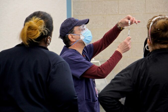 A staff member demonstrates how to prepare a dose at Philadelphia's COVID-19 vaccine center