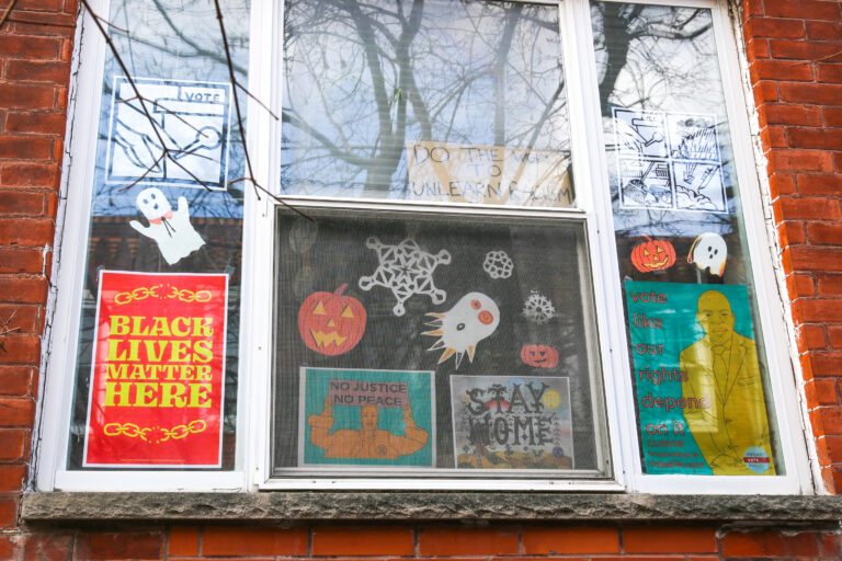 A Philadelphia household mixes political signs and holiday decor in their front windows during the turbulent fall of 2020. (Conrad Benner for WHYY)