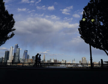 Pedestrians walk in Maxwell Place Park in view of midtown Mahattan Thursday, May 7, 2020, in Hoboken, N.J. (AP Photo/Frank Franklin II)