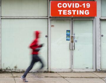 A person jogs by a COVID-19 testing site in Philadelphia, Monday, Jan. 25, 2021. (AP Photo/Matt Rourke)