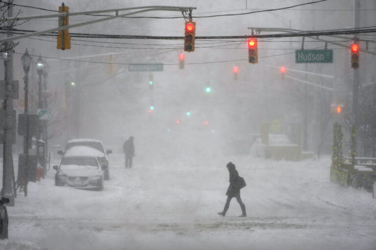 A few pedestrians are seen walking in the heavy snow and wind in Hoboken, N.J., Monday, Feb. 1, 2021. (AP Photo/Seth Wenig)