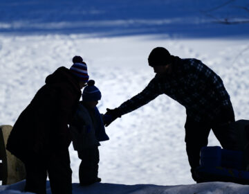 A couple helps a child on a snow covered embankment at Lorimer Park in Huntingdon Valley, Pa., Friday, Feb. 5, 2021. (AP Photo/Matt Rourke)
