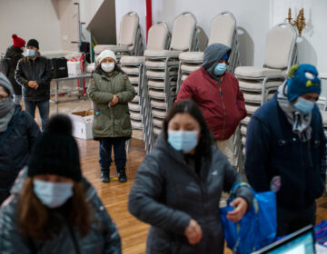 People wait to fill out forms at the community center Mixteca to receive food and get information about the COVID-19 vaccination during the coronavirus pandemic, Saturday, Feb. 13, 2021, in Brooklyn. (AP Photo/Eduardo Munoz Alvarez)