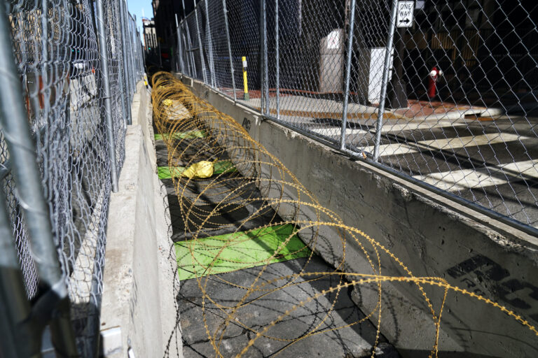 Concertina wire sits between fenced barriers outside the Hennepin County Government Center, Wednesday, Feb. 23, 2021, in Minneapolis, as part of security in preparation for the trial of former Minneapolis police officer Derek Chauvin. (AP Photo/Jim Mone)