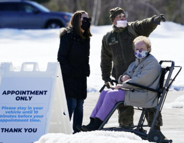 Sgt. Richard Grant of the Air National Guard helps point a patient in the right direction at a COVID-19 vaccination site at the Augusta Civic Center, Friday, Feb. 26, 2021, in Augusta, Maine. (AP Photo/Robert F. Bukaty)