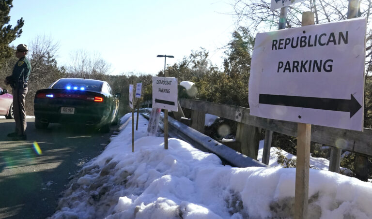 A sign directs Republican and Democrat legislators to their parking areas as a N.H. State Trooper watches the flow of traffic prior to a New Hampshire House of Representatives session held at NH Sportsplex, due to the coronavirus, Wednesday, Feb. 24, 2021, in Bedford, N.H. (AP Photo/Charles Krupa)