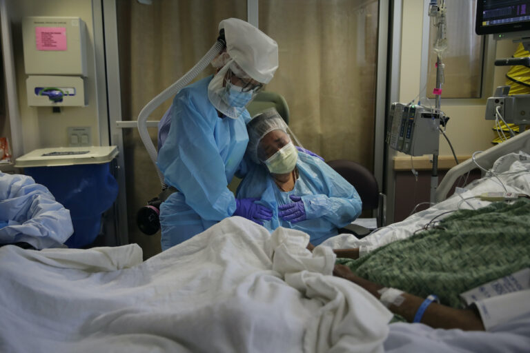 Romelia Navarro, right, is comforted by nurse Michele Younkin, left, as she weeps while sitting at the bedside of her dying husband
