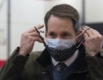Congressman Jim Himes, D-Conn., adjusts his two masks